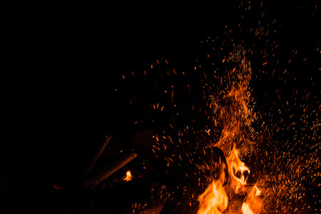 Sparks bounce off from a bonfire at night after a log thrown into it. Imagens