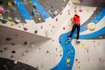 Aktive junge Kletterer Frau Klettern auf Indoor-Kletterwand.