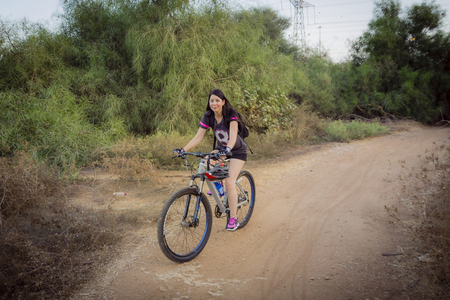 dirt road recreation: Woman riding a bicycle in the countryside and looking at camera.