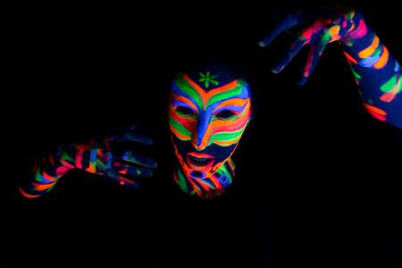 uv: Woman with make up art of glowing UV fluorescent powder. Stock Photo