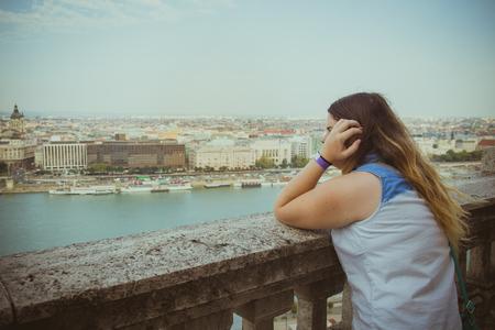 mujer mirando el horizonte: La mujer se inclina sobre la barandilla y mirando el horizonte, mientras que Budapest paisaje urbano en el fondo.