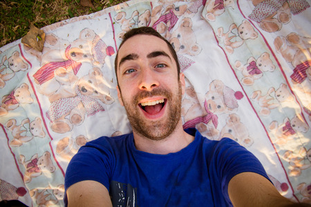 goofy: Young man lying on a sheet in the park and taking selfie picture with goofy smile. Stock Photo