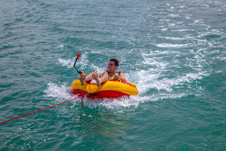 towed: Man sitting in inflatable ring towed by a boat in the water and recording himself Go Pro camera.