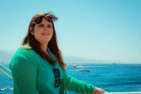 mujer mirando el horizonte: Vista de perfil de una mujer sonriendo mirando a otro lado en el mar.