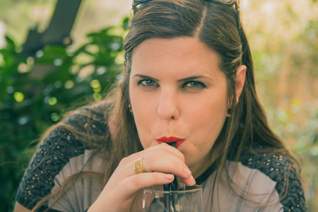 drinking straw: Young woman drink from a glass with drinking straw outdoor.