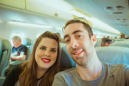 Happy couple taking selfie with smartphone or camera inside airplane.