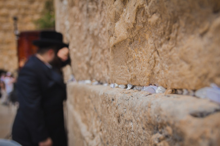Religious orthodox jew praying at the Western Wall in the old city of Jerusalem Israel. There are notes to God in the cracks between the bricks. Stock Photo