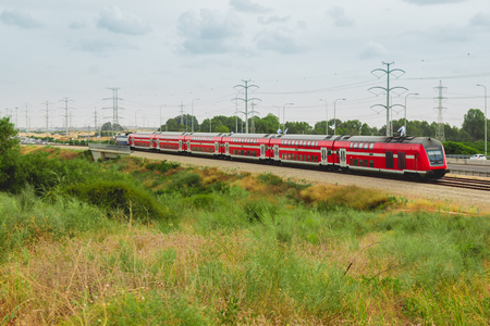 israeli: Red israeli passenger train in motion out of the city near Highway 4.