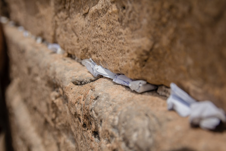 Notas a Dios en las grietas entre los ladrillos del Muro de los Lamentos en la ciudad vieja de Jerusalén, Israel. Foto de archivo
