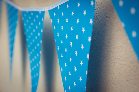 multiple birth: line of colorful blue party decorations flags with white stars illustration hanging from the wall.