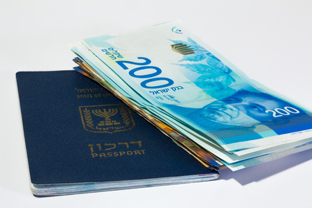 sheqel: Stack of israeli money bills of 200 shekel and israeli passport.