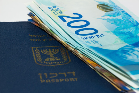 israel passport: Stack of israeli money bills of 200 shekel and israeli passport.