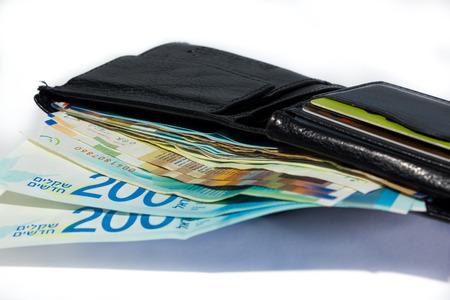 Stack of various of israeli shekel money bills in open black leather wallet. Stok Fotoğraf