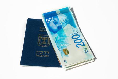 sheqel: Stack of israeli money bills of 200 shekel and israeli passport - Top view.