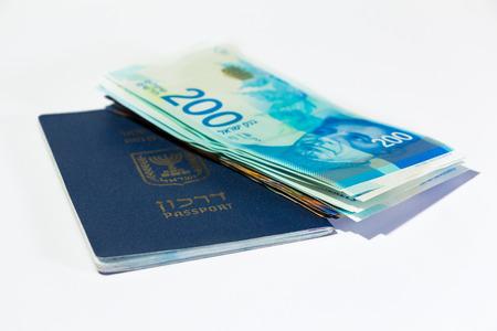 Stack of israeli money bills of 200 shekel and israeli passport.