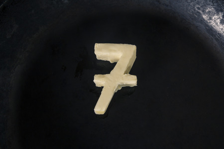 top 7: Butter in shape of number 7 on hot pan - Close up top view Stock Photo