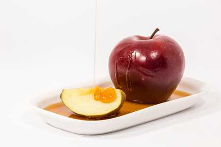 Pouring honey on red apple and red apple slice on white plate with honey isolated on a white background. Symbols of Jewish New Year - Rosh Hashanah.