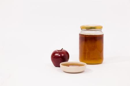 Red apple and jar of honey bowl of honey isolated on a white background. Symbols of Jewish New Year - Rosh Hashanah. Stock Photo