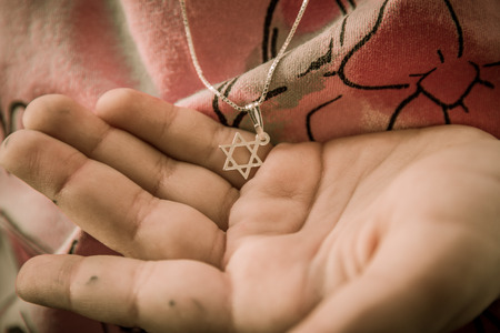 concern: Necklace with the Star of David on a girls hand.