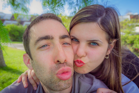 Couple having fun making duckface and taking selfie picture in the park.