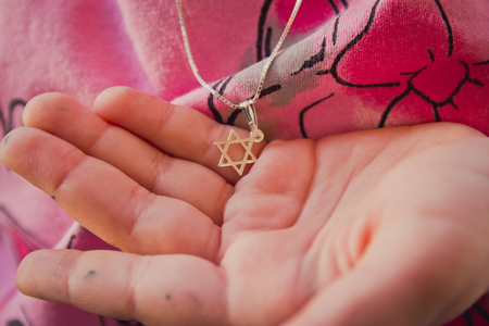 hebraism: Necklace with the Star of David on a girls hand.