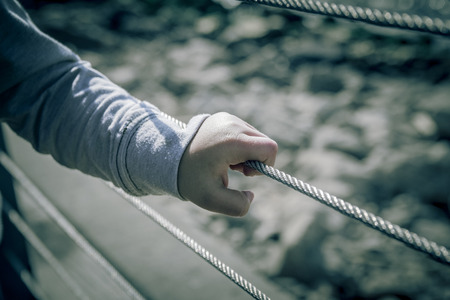 Young boy hand holding metal wire fence.