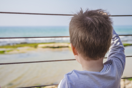 far away look: Young boy looks far away to the horizon from behind metal fence. Stock Photo