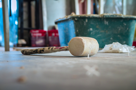 Wooden hammer on the floor in construction site. Stock Photo