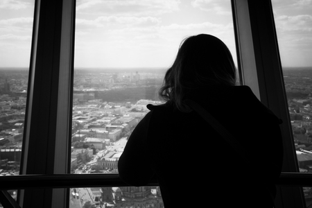 suspicion: Silhouette of back view of woman looking out of a window at the berlin city skyline. View from inside of the tv tower building.