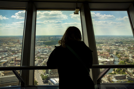 Silhouette of back view of woman looking out of a window at the berlin city skyline. View from inside of the tv tower building.