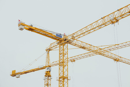 unfinished building: Many yellow construction cranes in winter day at the city of berlin.