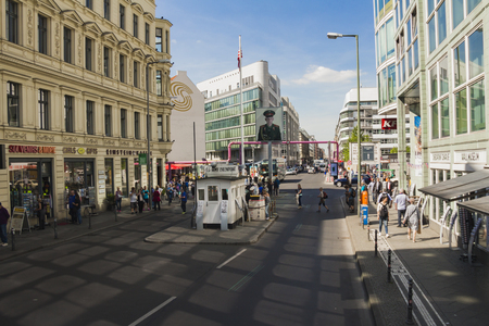 former: Berlin, Germany - May 17, 2017: Tourists at Checkpoint Charlie. former Berlin Wall border crossing point between East and West Berlin during the Cold War.