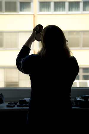 Back view of silhouette of a woman putting on makeup in front of a window.