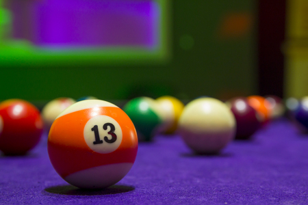 Billiard balls in a pool table. focus on the orange number 13 ball. Banque d'images