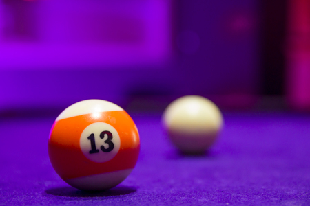 Billiard balls in a pool table. focus on the orange number 13 ball. Stock Photo