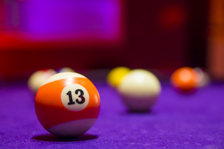 snooker halls: Billiard balls in a pool table. focus on the orange number 13 ball. Stock Photo