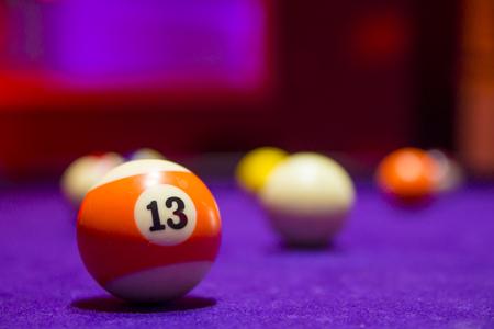 billiards halls: Billiard balls in a pool table. focus on the orange number 13 ball. Stock Photo