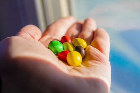 sugar palm: Man hand holding colorful chocolate candies buttons. Stock Photo