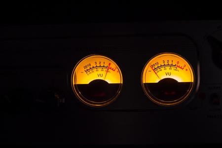Analog vu meters glowing on black background.