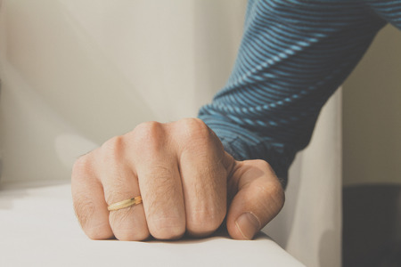 Man with a wedding ring squeezed his hand on white cloth background. Stock Photo