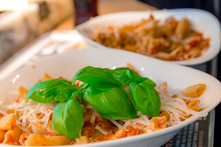 stirred: Penne pasta with tomato sauce and decorated with a mint leaf.