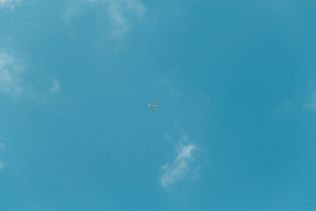 Glider gliding in blue sky from below. Stock Photo