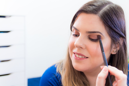 Woman applying makeup in her bedroom. She is smiling. Stock Photo