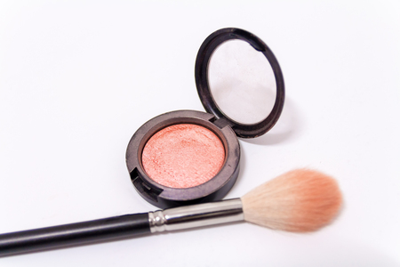Close up of makeup brush and blush box isolated on white background.