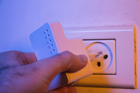 Man insert WiFi repeater into electrical socket on the wall. The device help to extend wireless network in home or office. Stock Photo