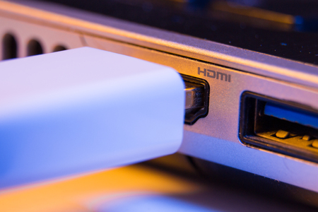 Closeup of HDMI cable plug inserted into port on the side of a laptop.