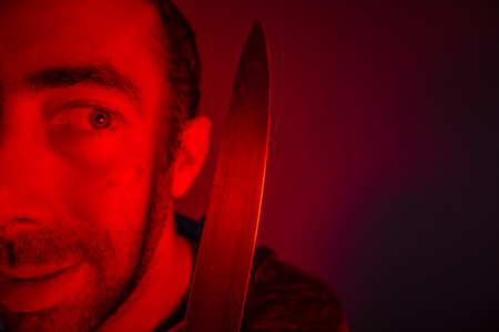 Closeup of sinister man looking at a knife that he holding.