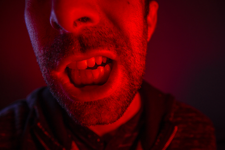 Man with angry facial expression screaming out loud. Close up portrait of a man shouting with mouth wide open. Stock Photo