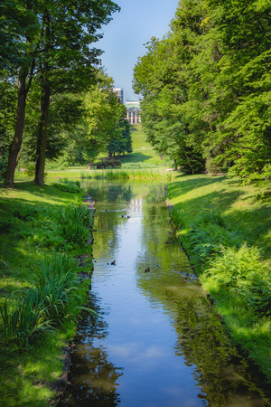 Beautiful stream with green grass and trees and the Belweder Palace at the horizon in Lazienki Park at Warsaw Poland.