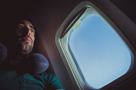 Pensive man with neck pillow seat by the window of an airplane.